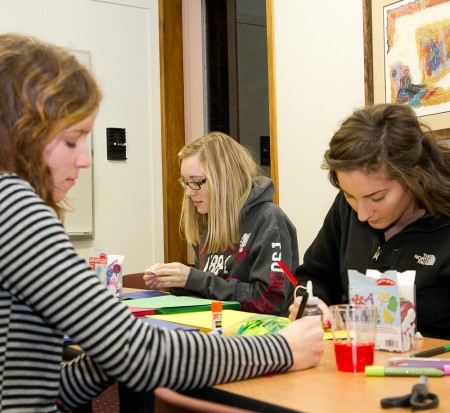 Spreading Holiday Cheer: Hannah Rillema, Jessica Swanson, and Emma Holmi, above from left to right, make holiday cards for soldiers overseas. Photo By: Brock Copus | Photographer