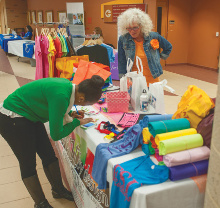 Local businesses offer t-shirts, blankets and other items as part of the Tribute to Women Expo. A discussion panel was held about women and gender roles in the work place. Photo By: Tori Thomas| Photographer